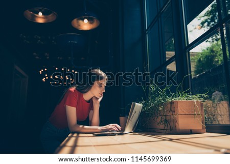 Attractive nice smiling dreamy young girl freelancer student wearing casual sitting in cafeteria, working remotely all day, typing business email