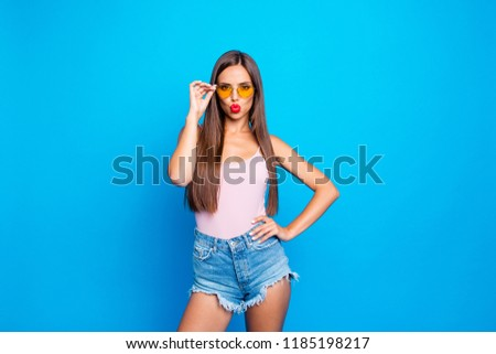 Attractive nice winsome adorable positive straight-haired cocky girl wearing tanktop, yellow sunglasses and jeans shorts, sending air kiss, isolated over bright vivid blue background
