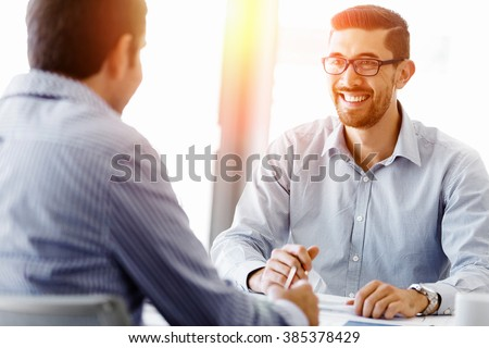 Attractive office worker sitting at desk #385378429