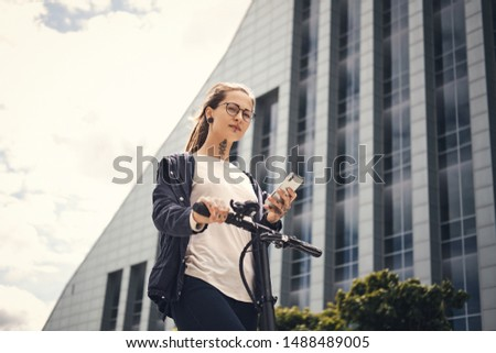 Attractive pensive girl is chatting by mobile phone while driving electro scooter near interesting building.