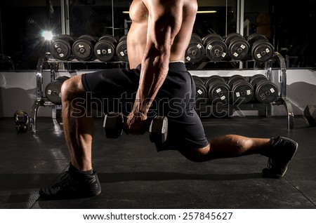 Attractive person working out in gym, dramatic lighting to knock out back ground light, shallow depth of field to bring focus to subject,