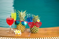 Attractive pineapples in stylish sunglasses and cocktail on swimming pool Tropical summer vacation concept. Happy sunny day