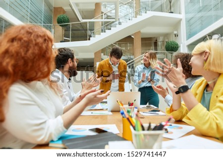 Attractive pleased man with thick beard, keeps hand on heart, bows head, expresses respect, thankful designers at table happily applaus