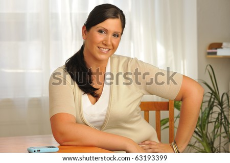 Attractive plus-sized model sitting at table with cell phone close at hand.