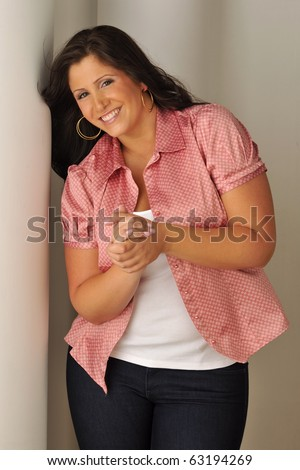 Attractive plus-sized model wearing red blouse in studio setting.
