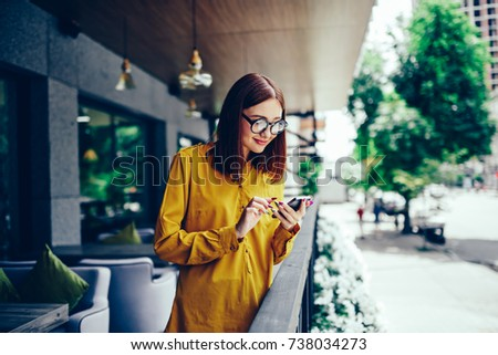 Attractive positive hipster girl in stylish eyewear sending funny messages to friends during recreation time outdoors.Happy cute female reading interesting news in website on modern smartphone #738034273