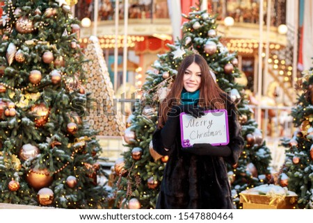 Attractive positive woman congratulating with Merry Christmas. Smiling girl spending time outdoors at Christmas fair. Panel, nameplate with congratulation in lady's hands. #1547880464