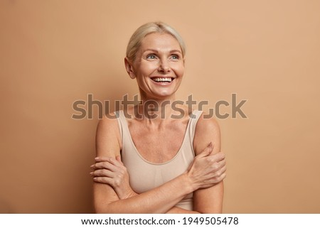 Attractive positive wrinkled fifty years old woman looks gladfully above keeps arms foded has well cared complexion healthy skin white teeth isolated over brown background. Beauty and age concept Foto stock ©