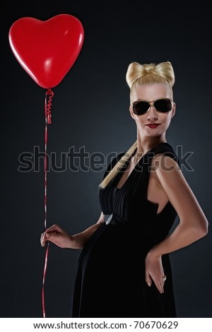 Attractive pregnant woman with a red balloon