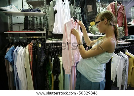attractive pregnant young girl in shop looks clothes