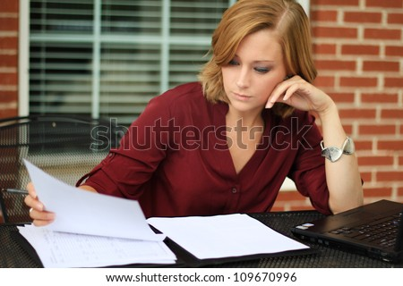 Attractive Professional Business Woman Writing and Reading Paperwork
