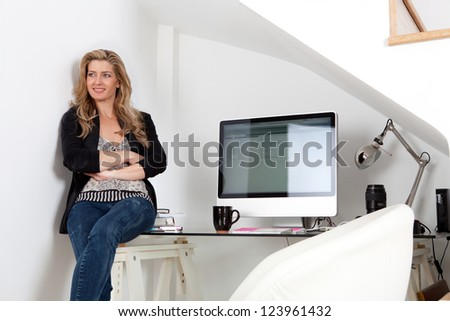 Attractive professional woman sitting on her work desk being proud and successful, next to her computer screen.
