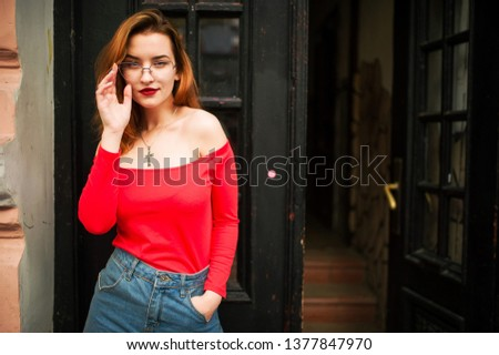 Attractive redhaired woman in eyeglasses, wear on red blouse and jeans skirt posing at street against old wooden door. #1377847970