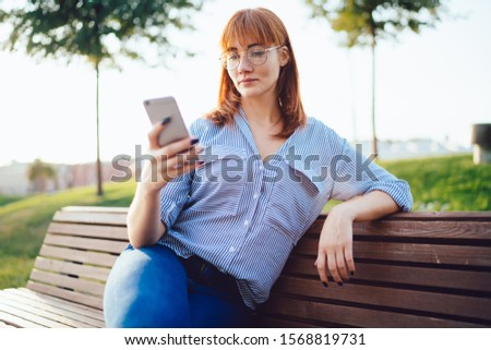 Attractive redhead woman in eyeglasses read articles from blog using mobile phone on free time in park, positive hipster girl update media content in social networks via smartphone and 4G internet