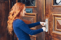 Attractive redhead woman unlocking a large old wooden front door with her key in a close up profile portrait