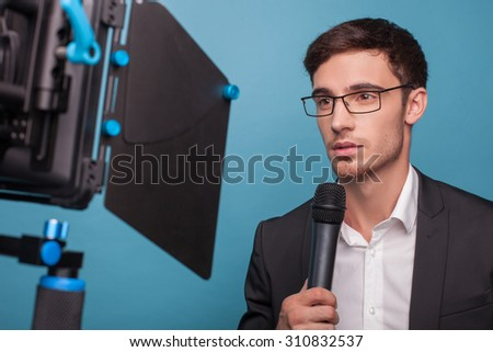 Attractive reporter is holding a microphone and telling news. The man is looking at the camera seriously. He is wearing suit and eyeglasses. Isolated on blue background
