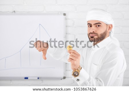 Attractive rich muslim male model in traditional Islamic clothing being serious and holding golden bitcoin and showing thumbs down. Horizontal shot. Financial problems, cryptocurrency, digital money. #1053867626
