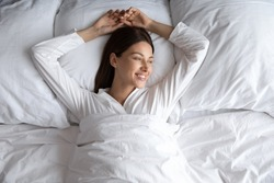 Attractive 30s carefree woman in comfy pyjamas lying down alone in comfortable bed after night enough sleeping woke up feels good top view. Enjoy fresh bedding, new sheet hotel room vacation concept