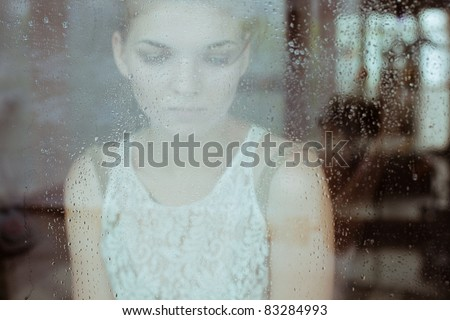 Attractive sad girl standing at the window watching the rain