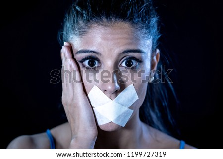 Attractive scared woman with taped mouth making in Silence Abuse Censorship Me too and Freedom of speech Concept Isolated on black background. #1199727319