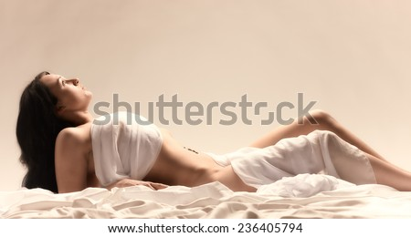 Attractive seminude woman wearing white fabric and she lying on the white bed sheets - tinted image