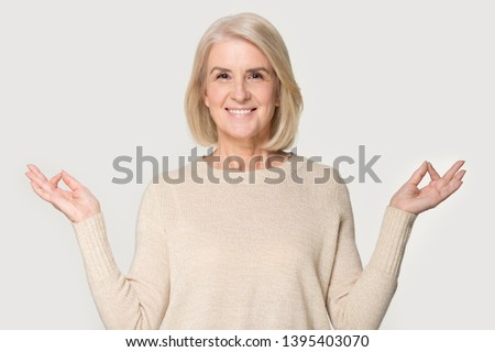 Attractive senior blond woman smiling feels good looks at camera folded fingers mudra gesture makes yoga exercise studio head shot isolated on grey background. No stress healthy female retiree concept