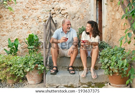 Attractive senior couple sitting on the steps of a luxury holiday villa with stone walls during a summer holiday, drinking wine and having a conversation. Mature people vacation outdoors lifestyle.