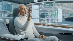 Attractive Senior Man Using Futuristic Augmented Reality Interface for Reading News and Checking Social Activity while Sitting on a Backseat of Autonomous Car. Self-Driving Van Rides on Public Road.