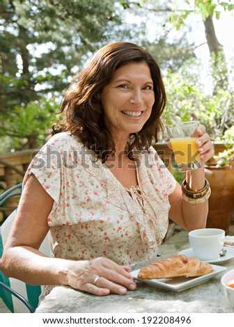Attractive senior woman at a table having breakfast in a luxury hotel garden during a sunny day on holiday. Mature people eating and drinking healthy food and relaxing, smiling. Outdoors lifestyle.