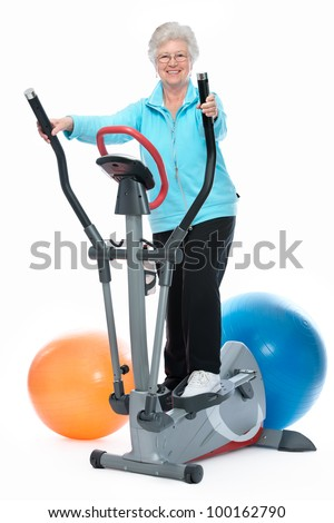 Attractive senior woman at health club, exercising on stepper - stock photo
