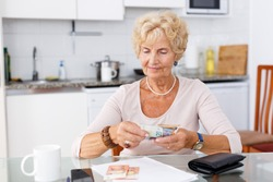 Attractive senior woman counting her cash sitting at the kitchen table