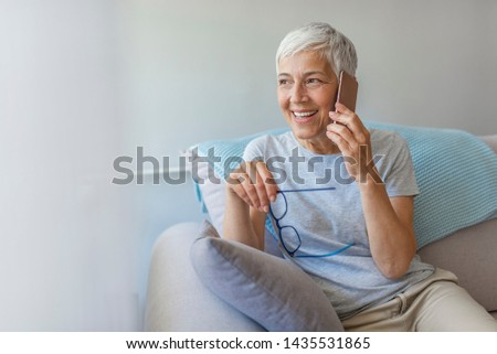 Attractive senior woman in eyeglasses talking on smartphone. Portrait of mature woman talking on phone. Portrait of woman sitting on sofa at home with mobile phone stock photo