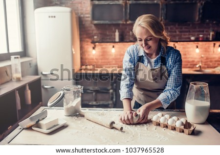 Attractive senior woman is cooking on kitchen. Grandmother making tasty baking.