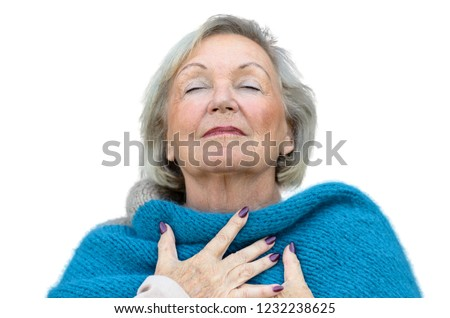 Attractive senior woman savoring the moment standing with her eyes closed and head tilted back with a serene expression as she clasps her chest with her hands #1232238625