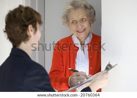 Attractive senior woman signing a document at her front door
