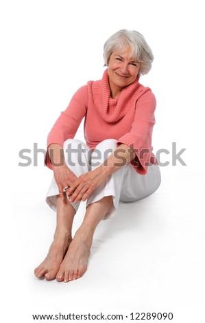 Attractive senior woman smiling sitting over a white background
