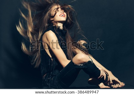 Attractive sensual young fashionable woman in stylish cloth and torn jeans with long beautiful hair sitting indoor on studio background, horizontal picture
