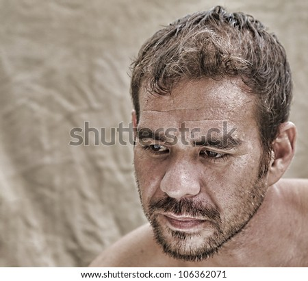 attractive serious man alone, looking down and thinking