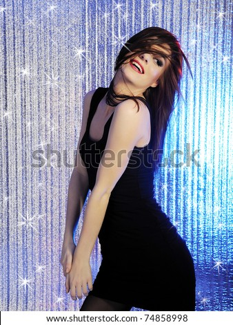 Attractive sexy woman clubbing, dancing in the disco and moving her hair