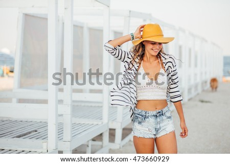 attractive sexy young woman with a summer yellow and a marine striped shirt moving ,dancing and smiling on the beach next to white beds