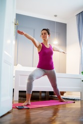 Attractive shape sporty middle aged woman doing yoga exercise Virabhadrasana II Pose at bedroom on a pink mat with tutorials from the internet.