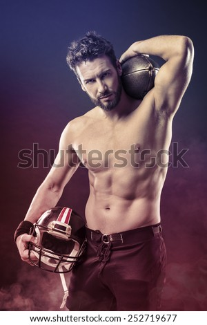 Attractive shirtless football player holding protective helmet and posing
