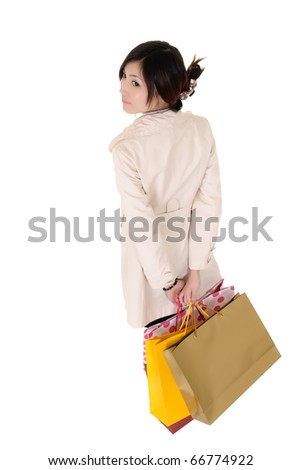 Attractive shopping woman holding bags and watching isolated over white.