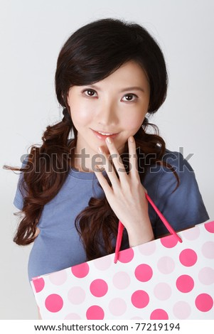 Attractive shopping woman of Japan holding bags and looking at you, half length closeup portrait on grey studio background. - stock photo