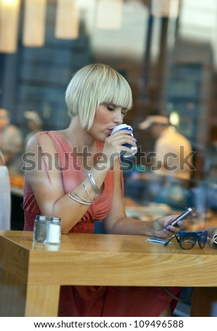 attractive sleepy woman drinking morning coffee in cafe window with mobile phone