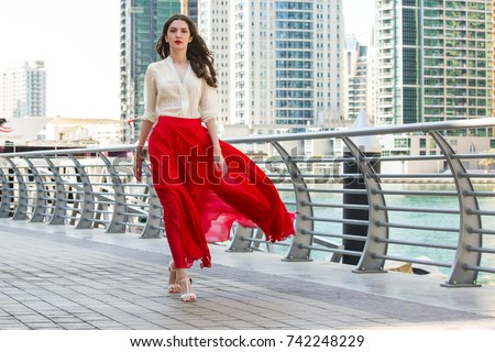Attractive, Slim, Beautiful And Brunette Girl Wearing White Shirt And Maxi Long Red Silk Fabric Skirt Fly And Wave In The Wind Walking Alongside Dubai Marina Middle East Fashion Concept - Shutterstock ID 742248229