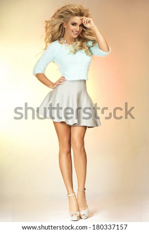 Attractive slim beautiful blonde woman posing in studio wearing elegant clothes, looking at camera.