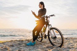 attractive slim woman riding bicycle, sport on morning sunrise beach in fitness sportswear, healthy lifestyle, listening to music on wireless earphones holding smartphone, relaxing smiling happy