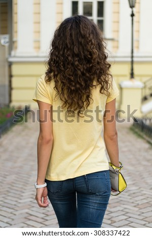 Attractive slim young woman with curly brown hair is walking on the old European city. She is wearing a yellow T-shirt and blue jeans, ladies handbag in her hand.