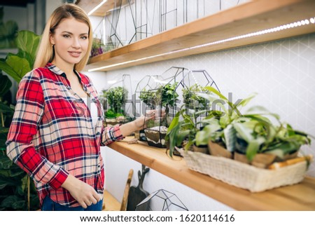 Attractive small business owner of a retail flower shop and garden center make composition of flowers. Caucasian woman florist entrepreneur shopkeeper love plants. Botany concept